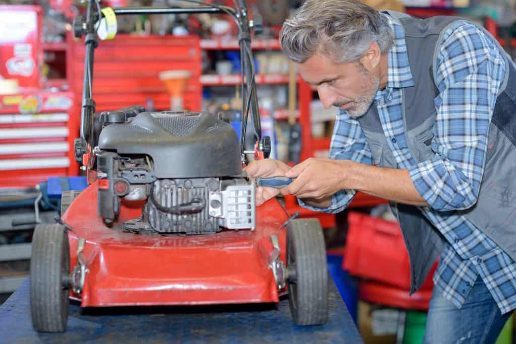 Small engine mechanic working on lawn mower due to the engine requiring starter fluid to start.